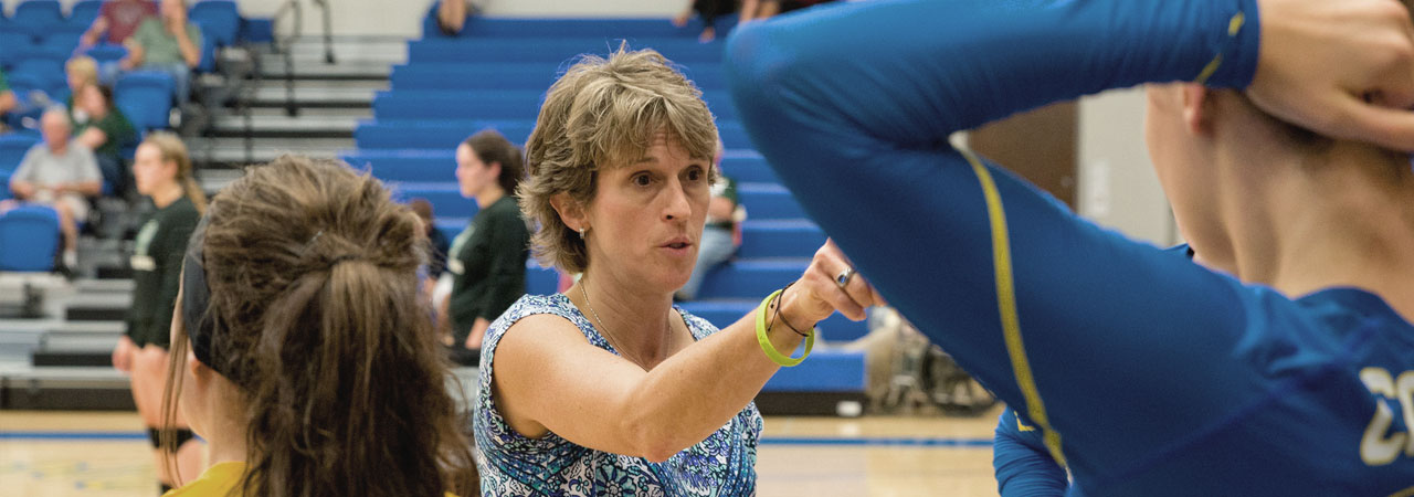 Volleyball Head Coach, Sue Sinclair, addressing player during a time out.